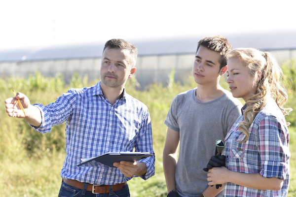Young people with instructor in agricultural field
