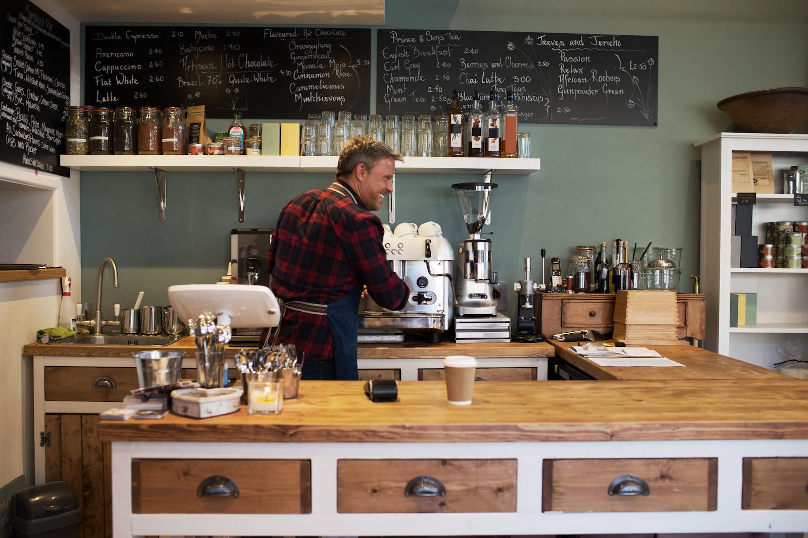 Male Barista Preparing Hot Drink In Coffee Shop